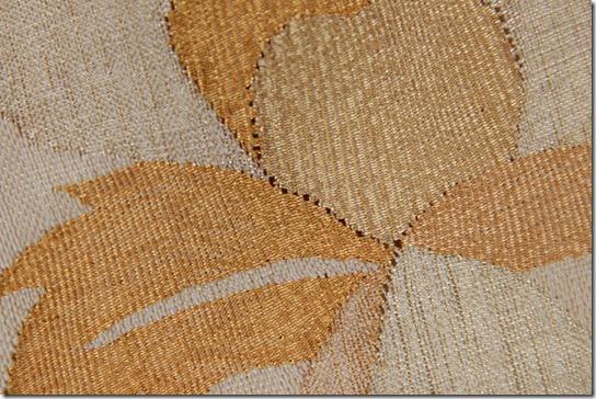 着物の帯、薄いベージュに唐花唐草文様の袋帯の把釣(はつり)